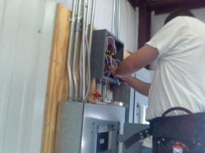A professional electrician services an electric panel during a project near Detroit, MI.