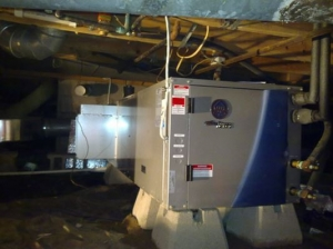 A large, standby generator is installed in a dimly-lit basement near Detroit, MI.