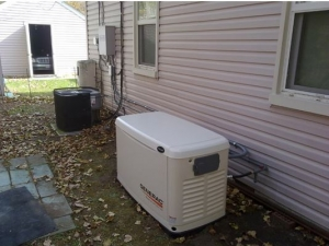 An exterior Generac generator is shown near a white-sided home near Detroit, MI.